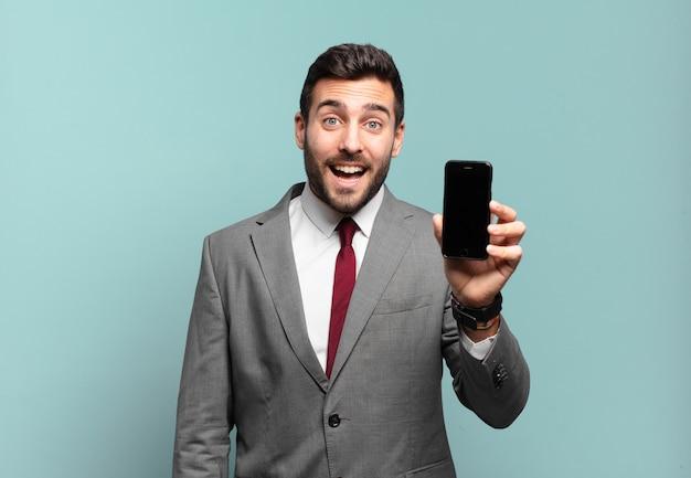 Jovem empresário parecendo feliz e agradavelmente surpreso, animado com uma expressão de fascínio e choque e mostrando a tela de seu telefone