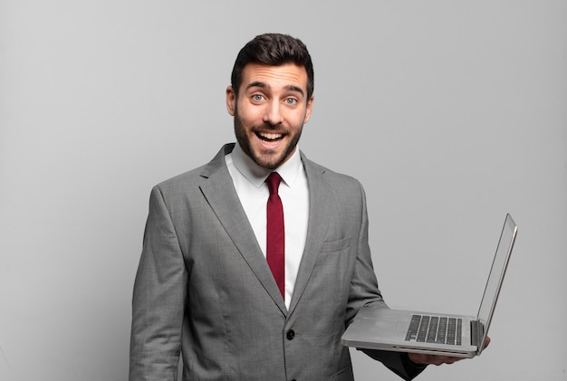 Jovem empresário parecendo feliz e agradavelmente surpreso, animado com uma expressão de fascínio e choque e segurando um laptop