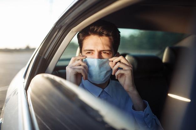 Jovem empresário pega um táxi e olha pela janela do carro, ajustando a máscara médica estéril. conceito de distância social.