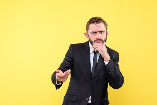 Jovem empresário pensando com gesto de dúvida em amarelo