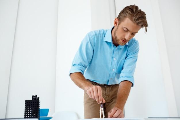 Jovem empresário pensativo confiante bonito trabalhando em pé no esboço de desenho de mesa. . interior de escritório moderno branco