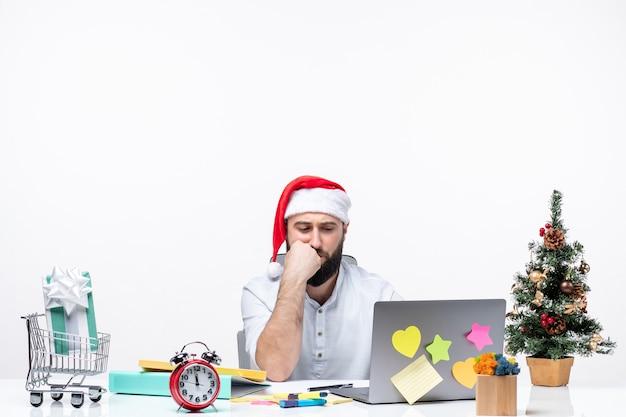 Jovem empresário pensativo e alegre no escritório, comemorando o ano novo ou o natal, trabalhando sozinho no fundo branco