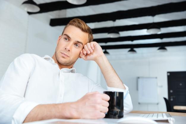 Jovem empresário pensativo e pacífico bebendo café e pensando no local de trabalho