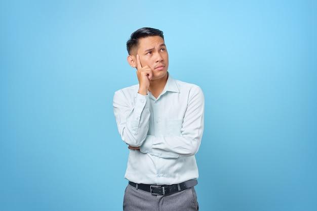 Jovem empresário pensativo pensando em perguntas sobre fundo azul