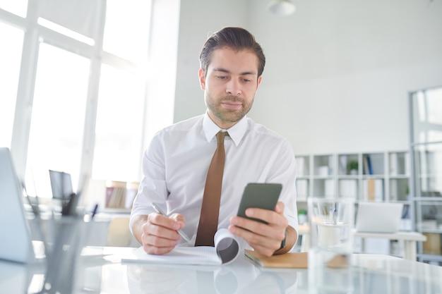 Jovem empresário percorrendo textos de negócios em smartphone e anotando algumas novas ideias