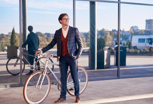 Jovem empresário positivo com uma bicicleta em pé perto de um edifício moderno
