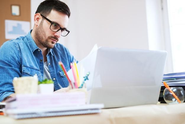 Jovem empresário preocupado e desgastado, olhando para a papelada na mesa do escritório.