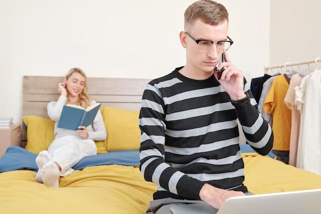 Jovem empresário preocupado falando ao telefone e verificando e-mails no laptop quando a namorada dele está lendo um romance em background