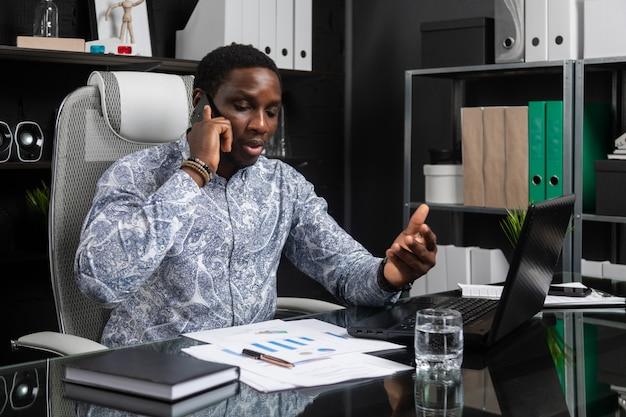 Jovem empresário preto falando celular sentado no computador mesa no escritório