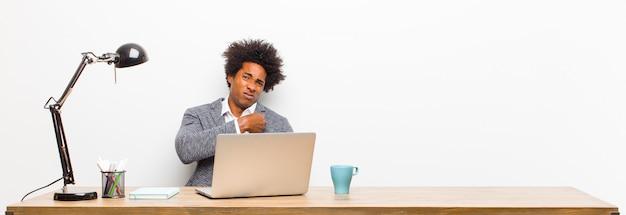 Jovem empresário preto olhando arrogante, bem sucedido, positivo e orgulhoso, apontando para si mesmo em uma mesa