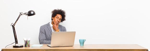 Jovem empresário preto olhando sério pensativo e desconfiado com um braço cruzado e mão nas opções de ponderação de queixo