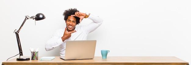 Jovem empresário preto se sentindo feliz, amigável e positivo, sorrindo e fazendo um retrato ou moldura com as mãos em uma mesa
