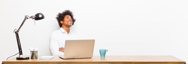 Jovem empresário preto se sentindo feliz, orgulhoso e esperançoso, pensando ou pensando, olhando para copiar o espaço com os braços cruzados em uma mesa