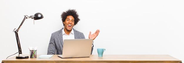 Jovem empresário preto se sentindo feliz, surpreso e alegre, sorrindo com atitude positiva, percebendo uma solução em uma mesa
