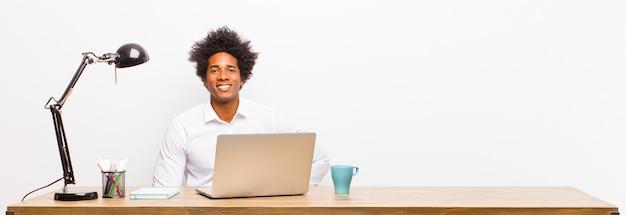 Jovem empresário preto sorrindo alegremente com uma mão no quadril e confiante atitude orgulhosa e amigável positiva