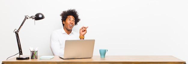 Jovem empresário preto sorrindo alegremente e olhando de soslaio, pensando, pensando ou tendo uma idéia sobre uma mesa