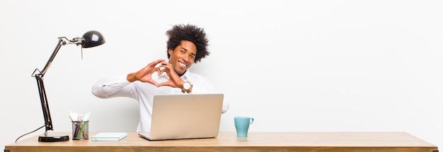 Jovem empresário preto sorrindo e se sentindo feliz, fofo, romântico e apaixonado, fazendo formato de coração com as duas mãos em uma mesa