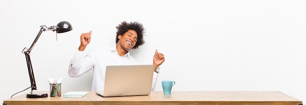 Jovem empresário preto sorrindo, sentindo-se despreocupado, relaxado e feliz, dançando e ouvindo música, se divertindo em uma festa em uma mesa