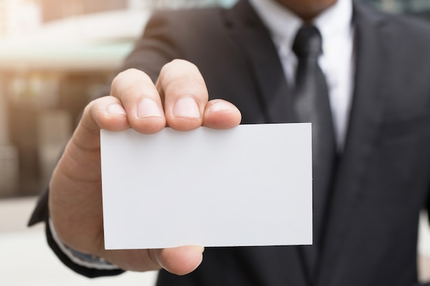 Jovem empresário que tira um cartão de visita em branco do bolso