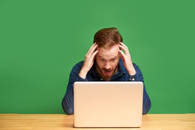 Jovem empresário ruivo chocado com uma camisa, segurando a cabeça entre as mãos e lendo notícias da internet no laptop