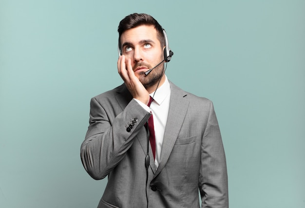 Jovem empresário se sentindo entediado, frustrado e com sono depois de uma tarefa cansativa, enfadonha e tediosa, segurando o rosto com o conceito de telemarketing