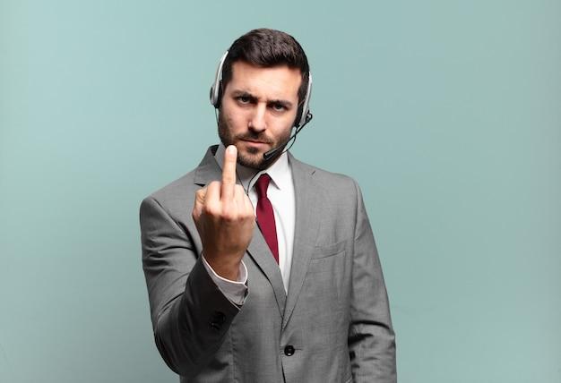 Jovem empresário se sentindo irritado, irritado, rebelde e agressivo, sacudindo o dedo médio, lutando contra o conceito de telemarketing