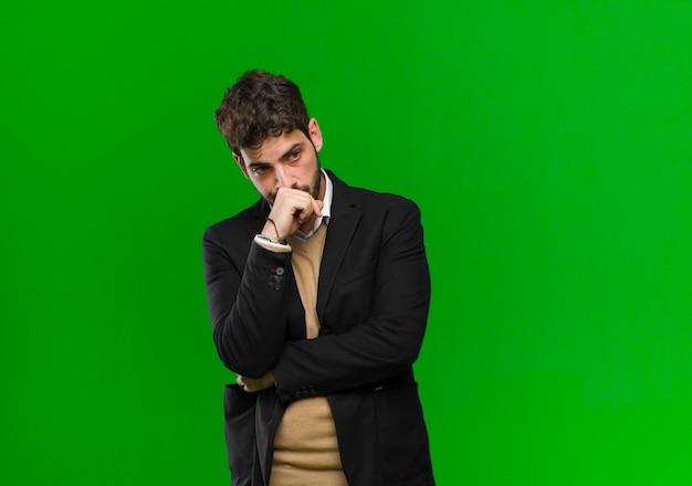 Jovem empresário se sentindo sério, pensativo e preocupado, olhando de soslaio com a mão pressionada contra o queixo contra a parede verde