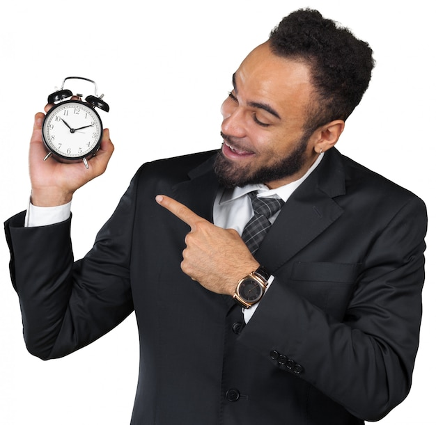 Jovem empresário segurando o despertador isolado no branco
