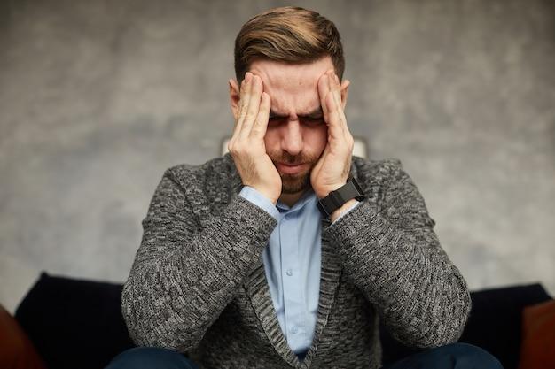 Jovem empresário segurando sua cabeça com as mãos, ele está com dor de cabeça e cansado do árduo dia de trabalho