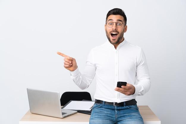 Jovem empresário segurando um telefone celular surpreso e apontando o dedo para o lado