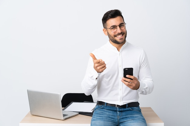 Jovem empresário, segurando um telefone móvel aponta o dedo para você