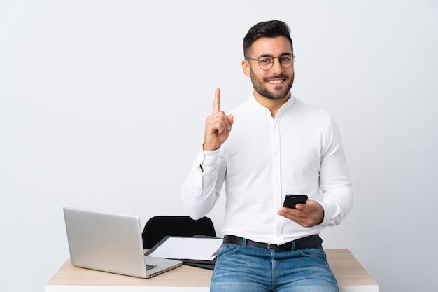 Jovem empresário segurando um telefone móvel apontando com o dedo indicador uma ótima idéia