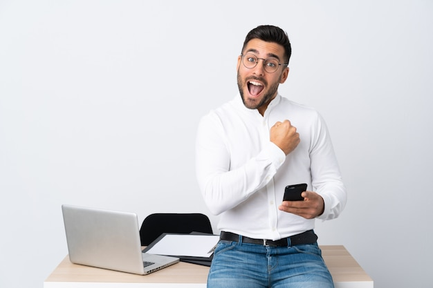 Jovem empresário segurando um telefone móvel comemorando uma vitória