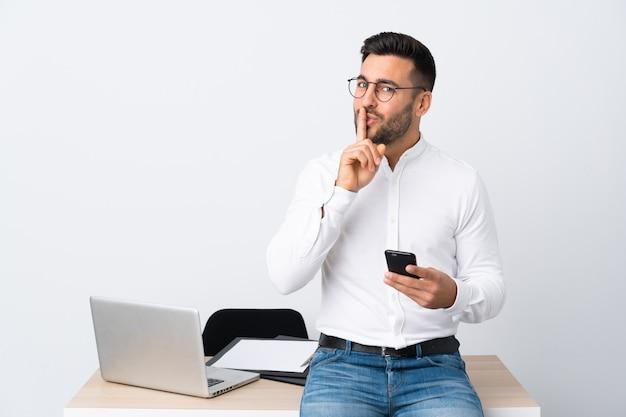 Jovem empresário segurando um telefone móvel, fazendo o gesto de silêncio