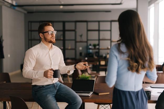 Jovem empresário segurando uma xícara de café e se comunicando com seu colega