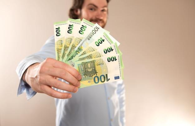 Jovem empresário segurar notas de 100 euros em dinheiro, isoladas em um fundo cinza.