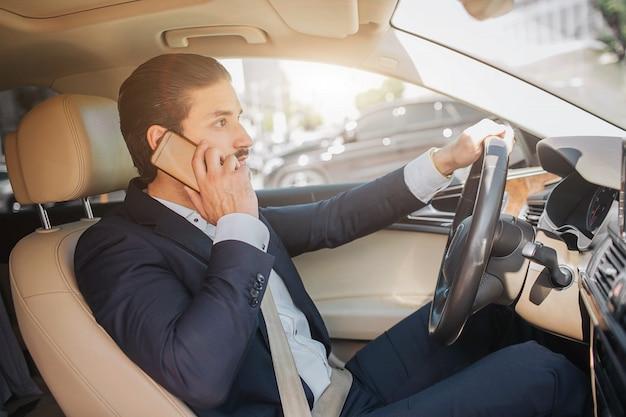 Jovem empresário senta-se em carro de luxo e fala no telefone. ele olha para a frente. cara dirige carro. ele segura uma mão no volante. está ensolarado lá fora.
