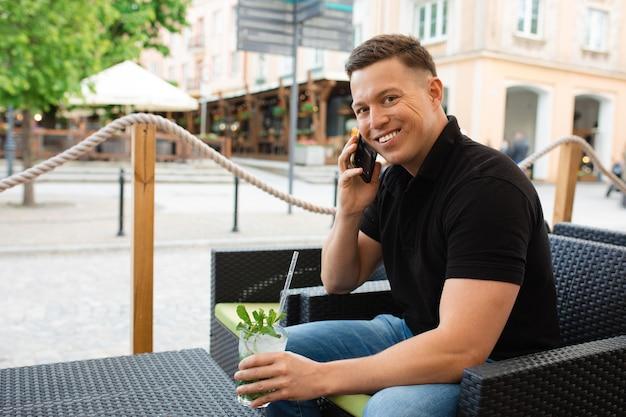 Jovem empresário sentado à mesa de um café de rua com um coquetel mojito refrescante