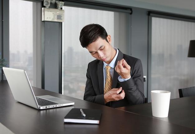 Jovem empresário sentado à mesa e vestindo terno