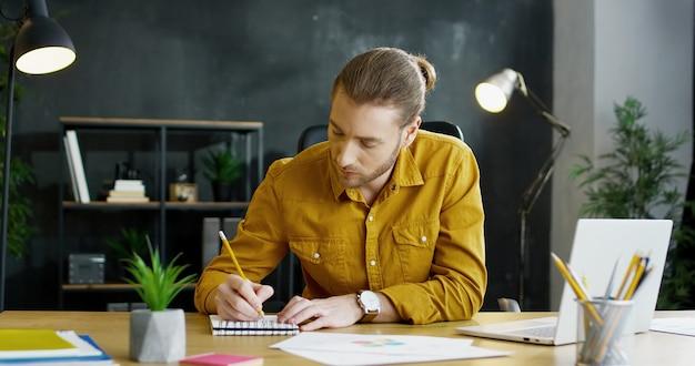 Jovem empresário sentado à mesa no escritório e escrevendo notas no caderno, trabalhando no computador portátil.