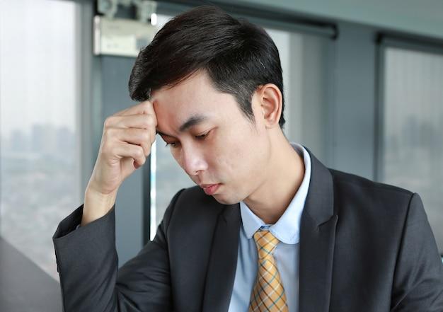 Jovem empresário sentado à mesa no local de trabalho no escritório com dor de cabeça ou grave