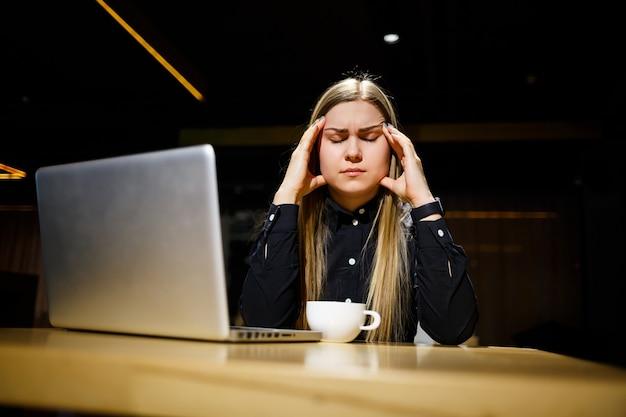 Jovem empresário sentado em frente ao computador com dor de cabeça devido a um longo dia de trabalho