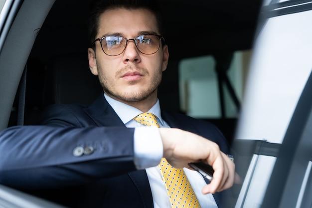 Jovem empresário sentado no banco de trás do carro, enquanto seu motorista dirige o automóvel