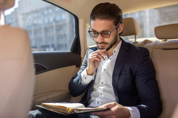 Jovem empresário sentado no carro e pensando. isso é luxo. ele mantém o caderno aberto. uma mão está no queixo. está ensolarado lá fora.