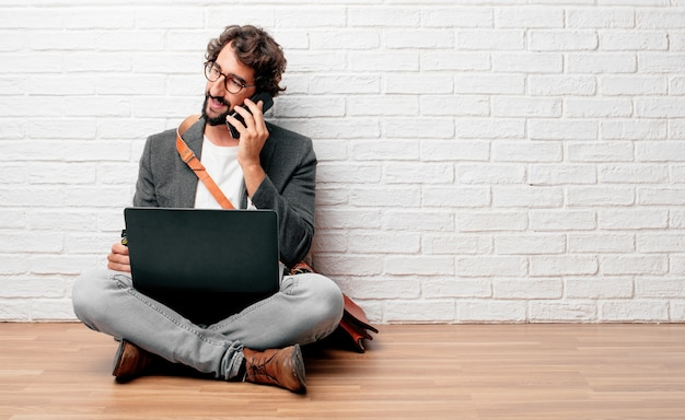 Jovem empresário sentado no chão com um laptop