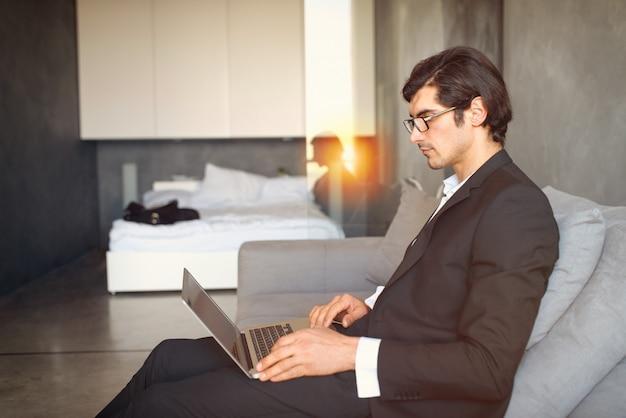 Jovem empresário, sentado no chão enquanto trabalhava em casa com um laptop
