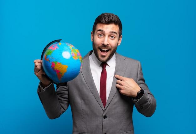 Jovem empresário sentindo-se feliz, surpreso e orgulhoso, apontando para si mesmo com um entusiasmo