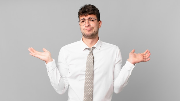Jovem empresário sentindo-se perplexo e confuso, duvidando, ponderando ou escolhendo diferentes opções com expressão engraçada