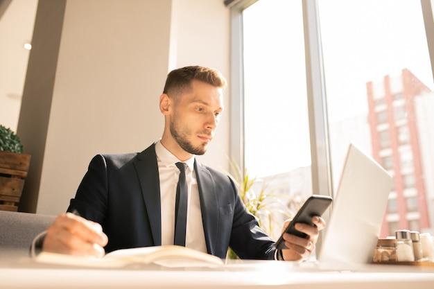 Jovem empresário sério concentrado em rolar a tela no smartphone enquanto olha os lembretes de compromissos