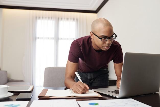 Jovem empresário sério de óculos verificando e-mails ou relatórios na tela do laptop e fazendo anotações no planejador